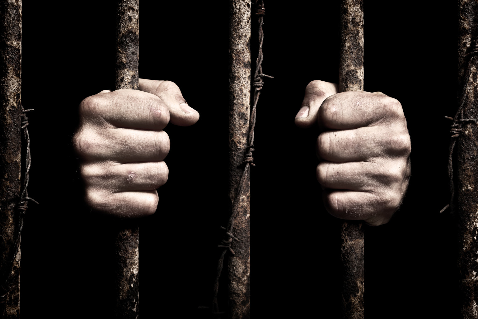 hands behind bars in prison